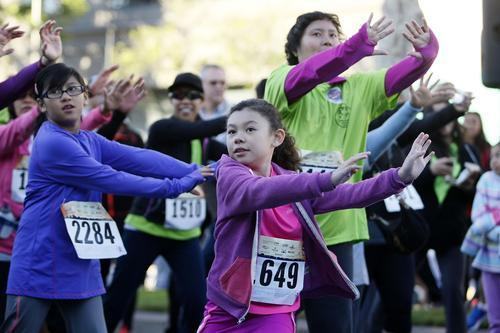Carly Gallegos, 7 of Palmdale, center, braved to cold and warmed up before running in the 6th annual Glendale News-Press 5K Downtown Dash & Walk on Brand Boulevard in Glendale on Sunday.
