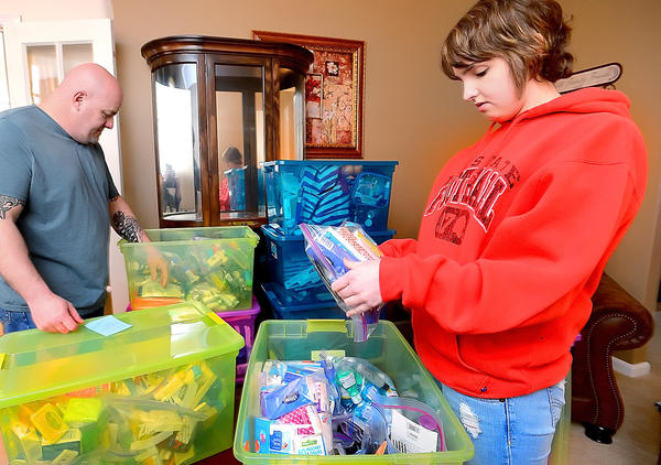 Alexis 'Lexi' Jarman, 17, and her father, Todd Jarman, stock supplies for Angel Bags in plastic containers at their Boonsboro home. The bags will be filled with clothing, toiletries and Bibles that will be distributed to family members of patients at R Adams Cowley Shock Trauma Center in Baltimore, where Lexi was treated after an accident in February 2012.