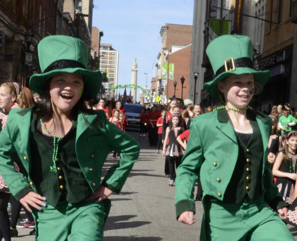 Dressed as leprechauns, Greta Cover, left, and Bailey Bartel with the Teelin School of Irish Dance from Columbia, dance down Charles Street at the annual St. Patrick Parade on March 10.