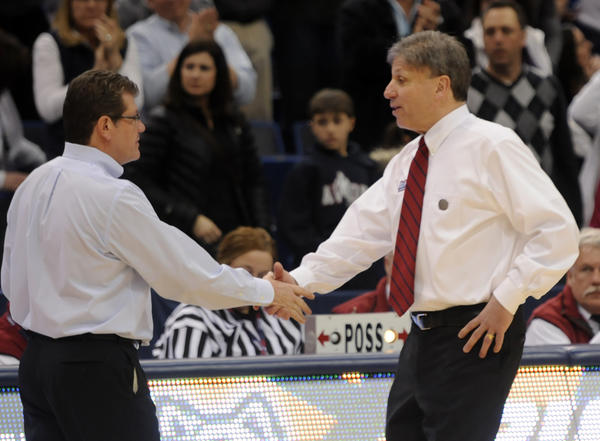 UConn coach Geno Auriemma, left, and DePaul Blue Demons coach Doug Bruno shake hands after the Huskies' 94-61 victory.