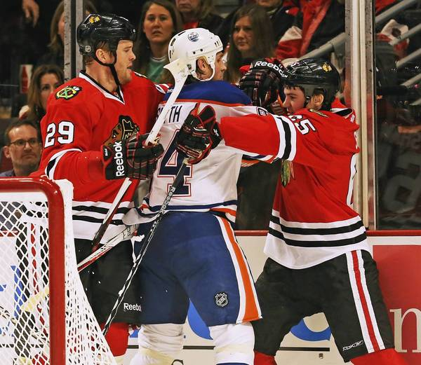 Bryan Bickell backs up Andrew Shaw as he gets entangled with the Oilers' Ryan Smyth.