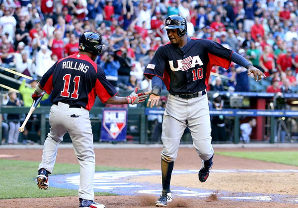 Adam Jones (10) of USA celebrates with Jimmy Rollins (11) after scoring a run against Canada.