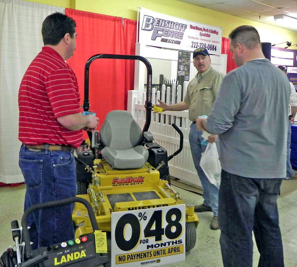 Tom Keilholtz, at rear, of Fairfield, Pa., and his friend Josh Brechbuehl, right, of Chambersburg, Pa., discuss the price of the Hustler Fast Trak Super Duty mower at the 30th annual Franklin County (Pa.) Builders Show at the Waynesboro Mall on Sunday. Also pictured at left is Lloyd Bier of Best Line Equipment of Shippensburg, Pa.