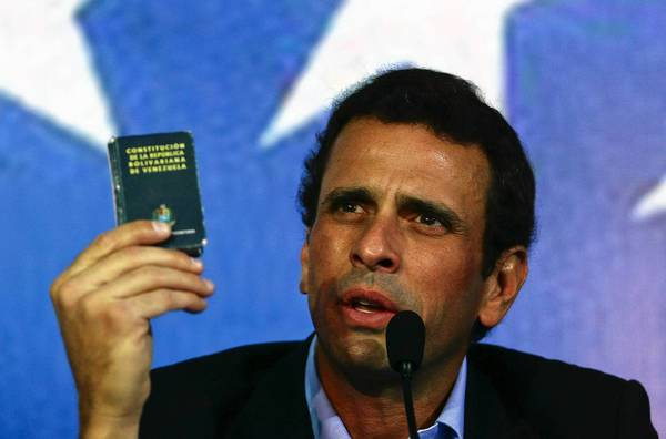Venezuelan opposition leader Henrique Capriles holds a copy of the constitution at a gathering in Caracas last week.