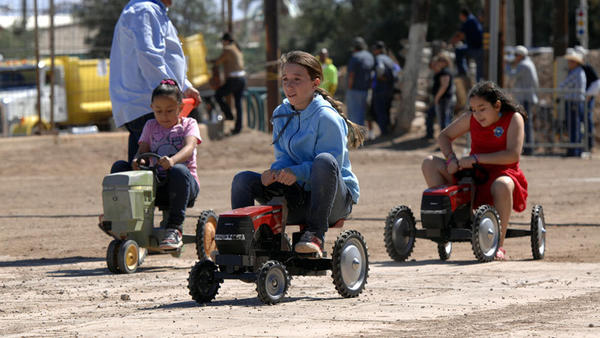 "Tiffany Steele (center), 12, competes in the pedal-powered tractor race during the Haul 'N Brawl event at the California Mid-Winter Fair & Fiesta in Imperial on Sunday. Steele, who loves to ride bikes, said of her winning the race, ""It's awesome to win."""