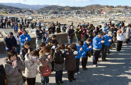 People observe a moment of silence facing the sea during a rally at the time when the magnitude 9.0 earthquake struck off Japan's coast in 2011 in Iwaki, Fukushima prefecture, on March 11.