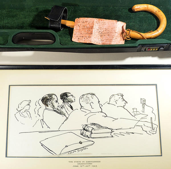 The cane used in a 1964 manslaughter trial moved from Baltimore to Hagerstown is on display at Washington County Museum of Fine Arts. Also shown is a sketch by artist Aaron Sopher at the time of the trial.