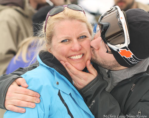 Becky Smits of Traverse City (left) pauses for a photo just as Brian Lapinski of Detroit photo-bombs her with a kiss Saturday at the Brewski celebration at Boyne Highlands. When asked, who he was, Smits said she had no idea.