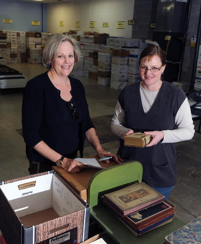 Laura Mullaly, of Pinehurst, left, and President Mary Anderson, of Hampden, sort and pack books in the warehouse as they prepare for the annual Smith College Book Sale next week.