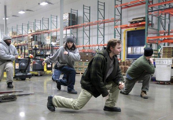 Employees exercise before the start of a shift at Organically Grown Co.'s warehouse in Gresham, Ore.