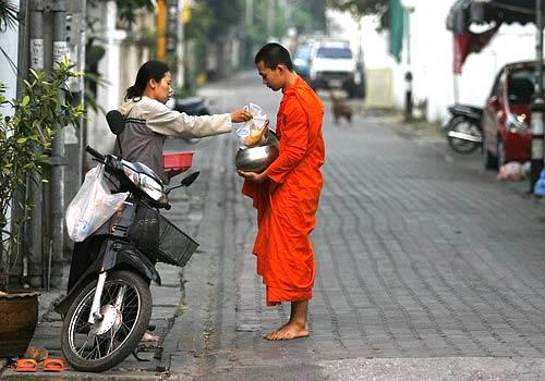 A woman offers food to a monk in the early morning hours in Chiang Mai, Thailand.