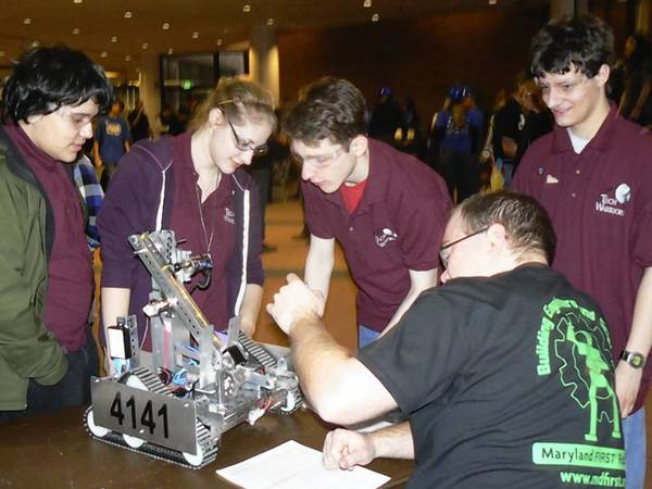 Havre de Grace High School Spears and Gears Robotics Team members, from left, Kenny Hallock, Allison Grabowski and Tucker Barnes and team mentor Tim Corbin watch as their robot goes through inspection at the recent FTC Maryland Championship. The team placed 14th overall and fourth among public schools entered.