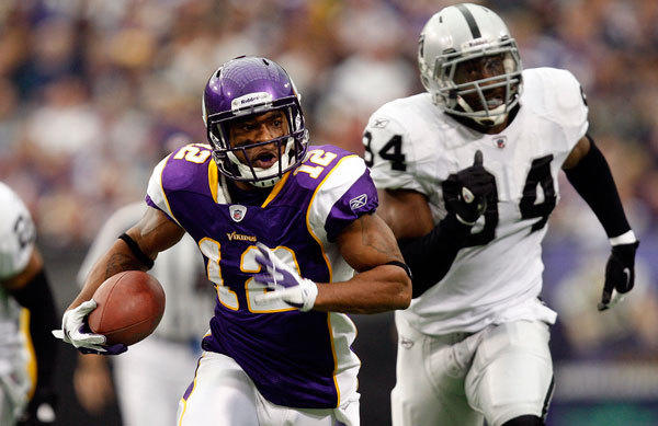 Minnesota Vikings receiver Percy Harvin (12) carries the ball ahead of Oakland Raiders defensive end Jarvis Moss (94) during the first half of their NFL football game in Minneapolis November 20, 2011.