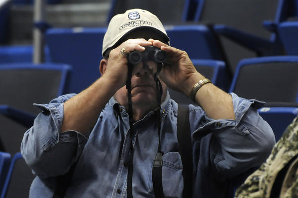 Joe Manes, a UConn fan, uses the binoculars he brought with him to watch the Huskies play in the Big East women's basketball tournament semifinals at the XL Center in Hartford, to check out the Notre Dame band playing a pregame tune.