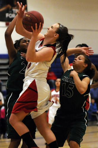 Kelly Flanigan of Cromwell splits the defense of Amanda Stewart, left, and Catherine Cruz of Weaver during the first half of their Class M basketball semifinal at Plainville High School Monday night. Cromwell is still undefeated and headed to the championship game after a 60-44 victory.