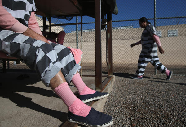 An immigrant inmate excercises while another sits on his bunk at the Maricopa County Tent City jail in Phoenix, Arizona. The striped uniforms and pink undergarments are standard issue at the facility. The tent jail, run by Maricopa County Sheriff Joe Arpaio, houses undocumented immigrants who are serving up to one year after being convicted of crime in the county. Although many of immigrants have lived in the U.S for years, often with families, most will be deported to Mexico after serving their sentences.