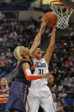 University of Connecticut center Stefanie Dolson, 31, is fouled by Syracuse Orange guard Elashier Hall, 2, during the first half. The University of Connecticut played the Syracuse Orange in the semifinals of the 2013 Big East Championship Monday night.