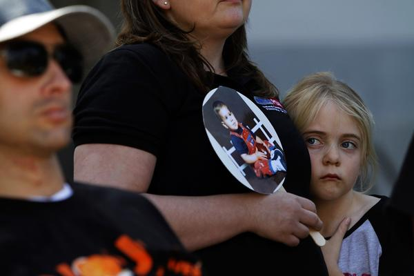 Katie Hansen, 8, stands next to her mother, Melanie, who holds a picture of Katie's uncle, Joey Rovero, who died in college of a prescription drug overdose.