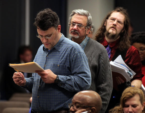 Donald Richie, left, and other people wait to ask questions about a new payment system and fees for the Chicago Transit Authority during a public meeting at CTA headquarters in Chicago.