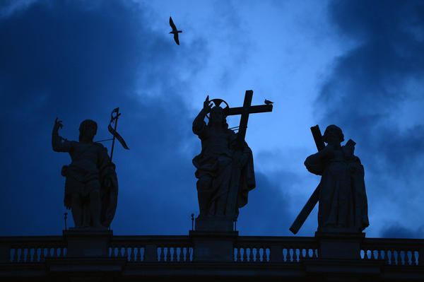 VATICAN CITY, VATICAN - MARCH 11:  A bird flies over statues on St Peter?s Basilica   on March 11, 2013 in Vatican City, Vatican. Cardinals are set to enter the conclave to elect a successor to Pope Benedict XVI after he became the first pope in 600 years to resign from the role. The conclave is scheduled to start on March 12 inside the Sistine Chapel and will be attended by 115 cardinals as they vote to select the 266th Pope of the Catholic Church.