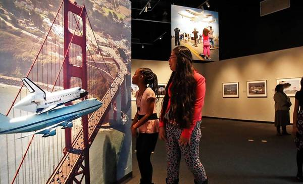 Fifth-grade students from Century Park Elementary School in Inglewood look at photographs in the latest exhibition related to the space shuttle Endeavour at the California Science Center. More than 1 million people have visited the Exposition Park museum since Endeavour made its debut just over four months ago, far surpassing officials' expectations.