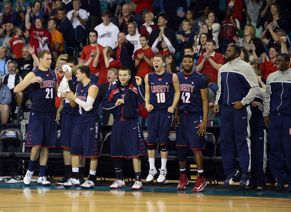 The Liberty bench celebrates during the championship game of the Big South Conference tournament.