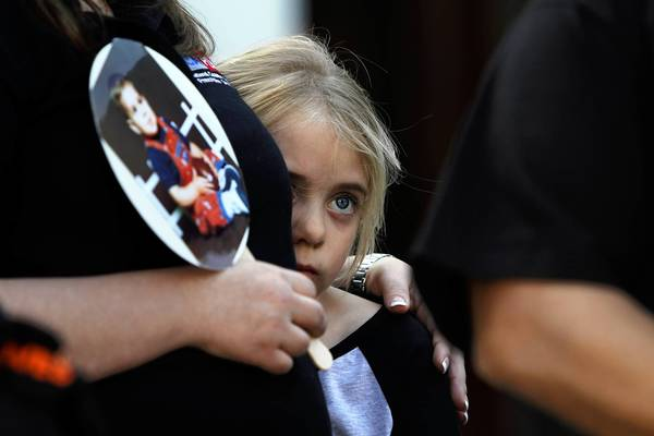 Katie Hansen, 8, stands next to her mother, Melanie, who holds a picture of Katie's uncle Joey Rovero, who died in college of a prescription drug overdose.