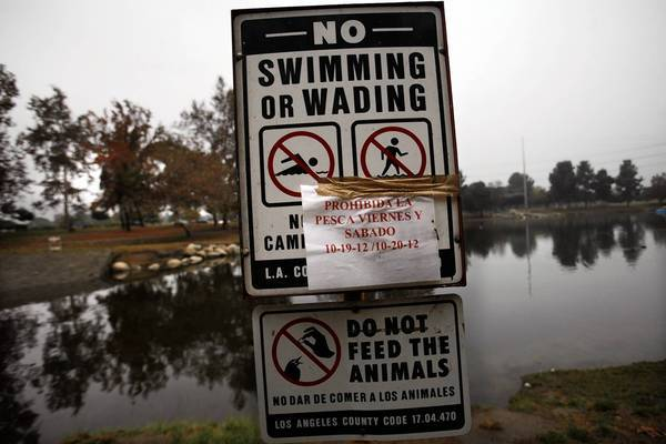 Signs warn against entering or fishing in storm water-fed Legg Lake in the Whittier Narrows Recreation area in Pico Rivera in 2012. L.A. County must comply with clean water regulations, including newly updated municipal storm water permits. Compliance will cost hundreds of millions of dollars, and failure to comply could lead to costly fines. The proposed fee would provide about $290 million a year.