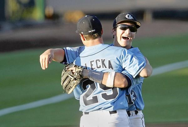 Corona del Mar High's Hunter Heckendorn, right, and pitcher Peter Walecka, left, share a hug after the Sea Kings beat Newport Harbor in Game One of a Battle of the Bay doubleheader at UC Irvine on Monday.