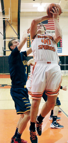 Harbor Springs senior Spencer Kloss (right) puts up a shot as Negaunees Brock Weaver defends during the third quarter of a Class C regional semifinal game Monday in Escanaba. Negaunee won, 64-37.