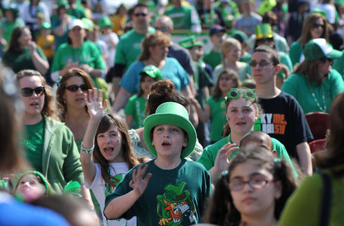 St Elizabeth Catholic School 3rd grade Jared King, 9, of Whitehall Twp. (foreground center) waves toward television cameras along North 19th Street, as he marches with classmates in the annual St. Patrick's Day parade in Allentown on March 18th, 2012.