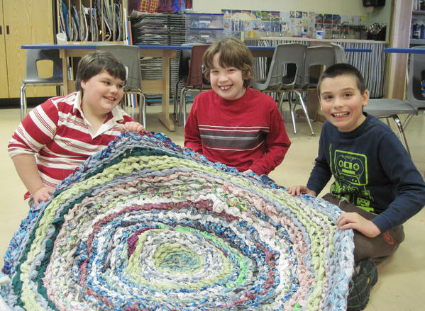 "Third-graders Bobby Blome and Brian Fryer help fourth-grader Cory Carlson show off one of the student-made rag rugs to be auctioned at Concord Academy Petoskey at 6:30 p.m. on Friday, March 15. The rugs were made by students in kindergarten through fourth grades. In addition, student-made painted silk scarves, tiled tables, mugs, trays, plates, clocks, pillows and other artwork will be sold.  The school will also auction themed baskets including ""Movie Night,"" ""Sleep over"" and ""Chocolate.""  The cost for a bid card and a dessert is $5. For more information call Concord Academy Petoskey at (231) 439-6800."