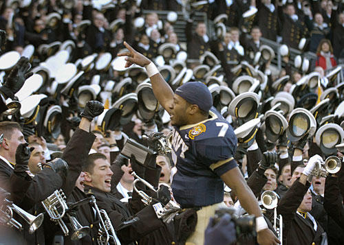 Navy senior Reggie Campbell conducts the Navy band in the playing of the school's alma mater after the Mids' 38-3 win over Army.
