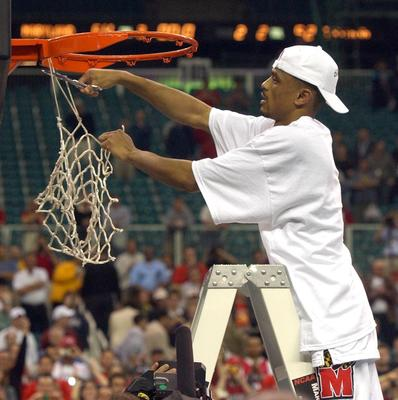 Terps guard Juan Dixon snips a part of the net in post-game celebration.