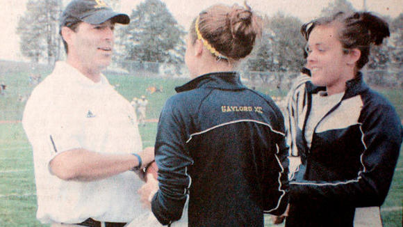During the 2007 season, Cleaver accepts the game ball from Gaylord cross-country runners Sloan Secord (l) and Wendy Holland before the Homecoming game.