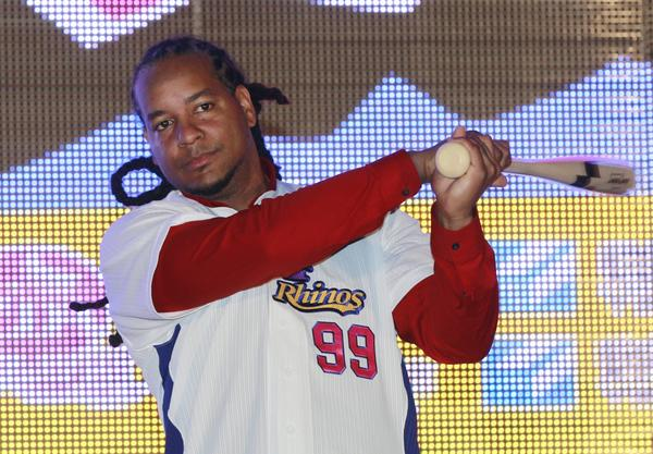 Former MLB star Manny Ramirez poses with an honorary baseball bat and new team jersey Tuesday after signing a short-term contract to play on the EDA Rhinos in Taiwan's professional baseball league.