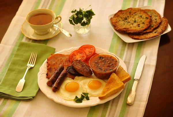 Clockwise from center, black and white pudding, bangers, rashers, tomatoes, baked beans, toast and fried eggs. Side plate of Irish boxty, upper right. Styled by Julie Rothman.