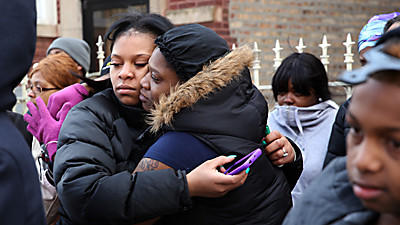 "Judy Young, whose 6-month-old daughter Jonylah was killed at 65th and Maryland Avenue in Chicago, visits the scene of the shooting surrounded by family and friends. Young has a tattoo with the words ""Love Live Life."""