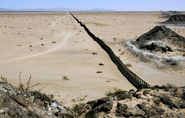 """Dubbed """"the longest fence,"""" this portion of the U.S. border wall stretches about 40 miles across the desert east of San Luis, Arizona. The Mexican state of Sonora is on the right."""