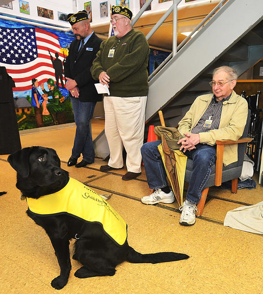 Trooper looks around for his next command Tuesday during an exhibition at Maryland Correctional Institution-Hagerstown, where inmates train dogs to help wounded and disabled veterans. The Ralph S. Tagg Chapter 14 of Disabled American Veterans represented by, from left, Doug Flanigan, Jerry Barnhart and Ernie Unger, presented a check for $2,000 to help fund the program.