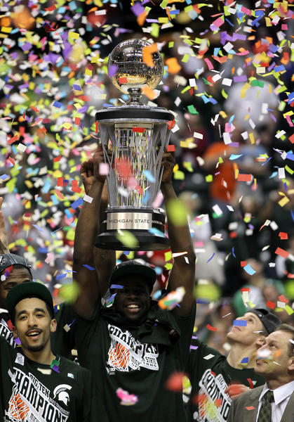 Brandon Wood, Draymond Green and Michigan State coach Tom Izzo celebrate with the conference championship trophy after they won 68-64 against Ohio State in 2012.