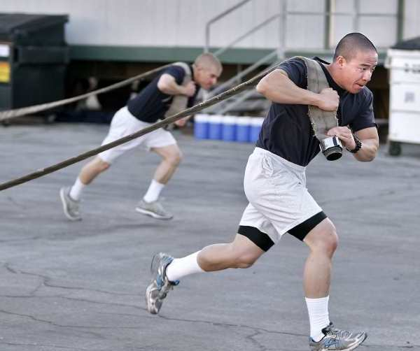 Burbank Fire Dept. recruit Hai Nguyen, front, pulls a hose during training at the training academy in Burbank. The 14-week training began with 11 recruits and now is down to nine.