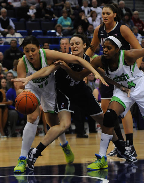 University of Connecticut guard Kelly Faris, 34, center, battles Notre Dame Fighting Irish forward Natalie Achonwa, 11, left, and Notre Dame Fighting Irish forward Ariel Braker, 44, during the first half. The University of Connecticut played Notre Dame in the final game of the 2013 Big East Championship Tuesday night.