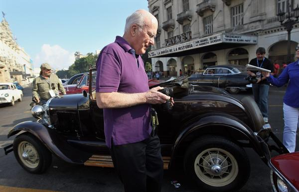Sen. Patrick J. Leahy (D-Vt.) takes pictures of old vehicles outside National Capitol building in Havana, Cuba.