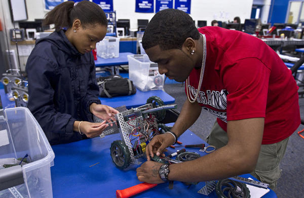 N.H.students Shawmonique Ferguson 19 and Kamilah Walker 17 are making some repairs on their robot after a field test game...Dutch students are visiting the New Horizons Regional Education Center in Hampton today as part of an ongoing robot-building project. In 2010 New Horizons students won several awards for robot competitions. Both teams have built new robots that are ready to compete in North Carolina next weekend.