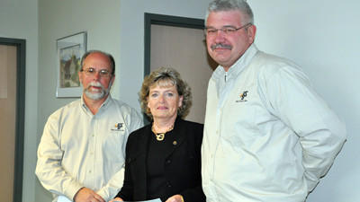 Somerset County General Authority Chairwoman Lladel Lichty is all smiles when she receives a hefty royalty check from PBS Coals Inc. representatives, spokesman Hank Parke, left, and land manager John Weir.