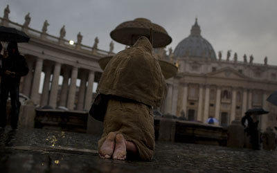 A man prays outside St. Peter's Basilica on the first day of the conclave.