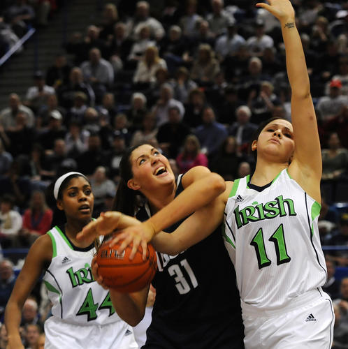 University of Connecticut center Stefanie Dolson (31) draws a foul from Notre Dame Fighting Irish forward Natalie Achonwa (11) as Notre Dame Fighting Irish forward Ariel Braker (44) looks on during the second half. The University of Connecticut played Notre Dame in the final game of the 2013 Big East Championship Tuesday night.