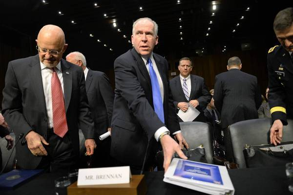 Director of National Intelligence James Clapper, left, and CIA Director John Brennan prepare to testify before the Senate Intelligence Committee in Washington.