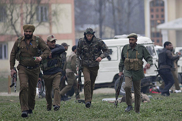 Indian police officers secure the area after a gun battle in Kashmir left five Indian paramilitary officers and two militants dead.